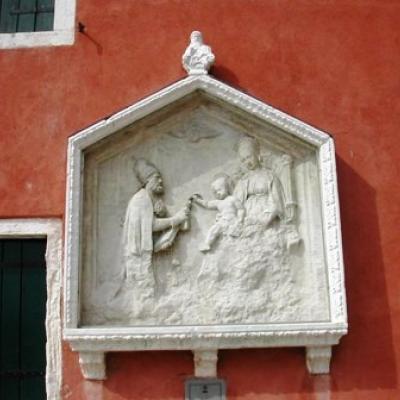 Gottesmutter mit Kind, das Petrus im Bischofsgewand den Schlüssel übergibt (Relief an einer Hauswand in Castello)