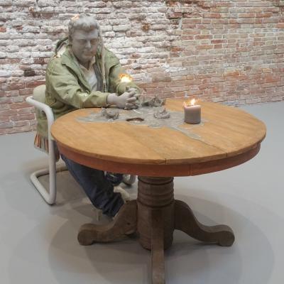 Urs Fischer als Kerze an einem Tisch sitzend